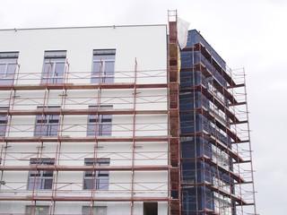 Malerarbeiten -  Baugerüst umhüllt Fassade eines Wohnhauses
