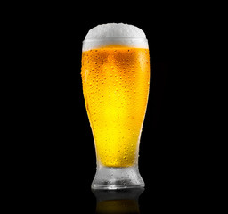 Beer. Glass of cold beer with water drops. Craft beer isolated on black background