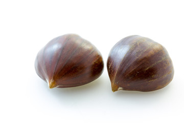 Two tasty uncooked chestnuts with white background