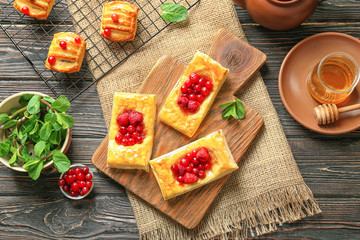 Cutting board and baking rack with pastries on wooden table