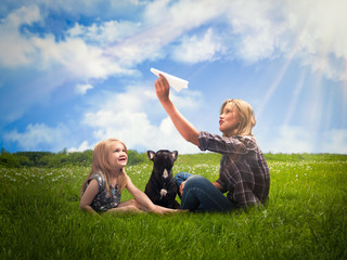 Lucky kids launch paper airplane. Green grass, blue sky, the rays of the sun. Girls play