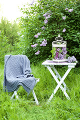 Cage with lilac flowers on table in beautiful garden