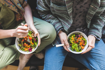 Couple eating healty salad at home on the sofa