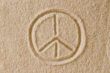 Peace Sign drawn in sand. Imprint and shape of the Pace Symbol in ocher grains of sand. Also a symbol for antiwar, love and counterculture, also used by hippies. Macro photo close up from above.