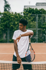 Confident young player holding tennis racket and looking away concentrated while standing on the court.