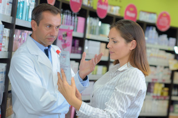 shop assistant helping woman choose in cosmetics store