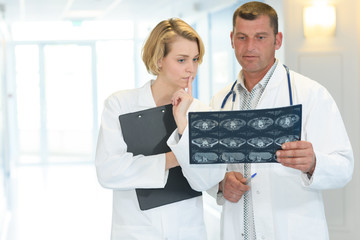 middle-age female and male doctor looking at x-ray