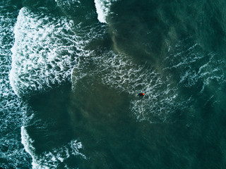 Aerial photo of a surfer swimming on waves on a stormy day