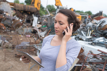 beautiful brunette on the phone at junk yard