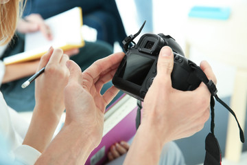 Male instructor holding digital camera during photography classes