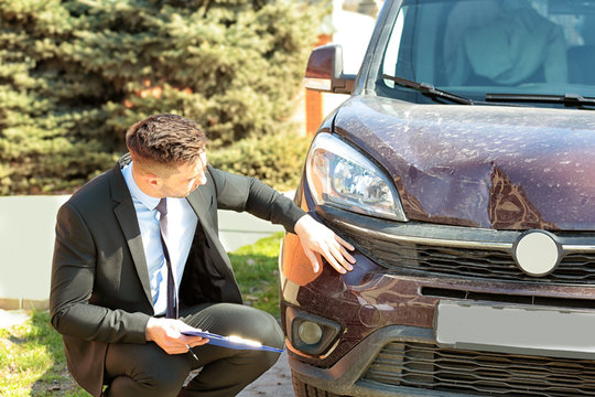 Loss adjuster inspecting car after accident