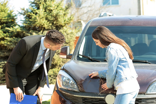Loss adjuster and young woman inspecting car after accident
