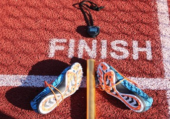 Stopwatch, baton and spikes at finish line