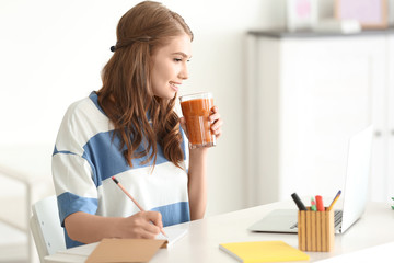 Weight loss concept. Beautiful young woman drinking healthy delicious smoothie and using laptop at home