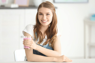Weight loss concept. Beautiful young woman sitting at table with healthy delicious smoothie