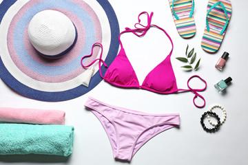 Colorful bikini and beach accessories on white background