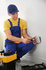 Electrician repairing socket indoors