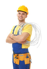 Young smiling electrician with bunch of wires on white background