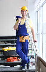 Smiling young electrician with bunch of wires and toolbox standing on stairs indoors