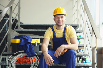 Young smiling electrician sitting on stairs indoors