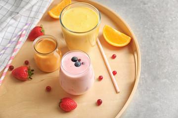 Fresh orange and blueberry yogurt smoothies on wooden tray