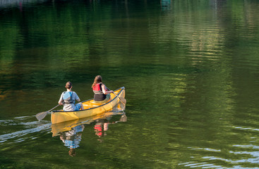 Couple paddling in yellow canoe on tree lined lake
