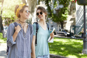 People and relationships concept. Sweet couple of lesbians walking togehter outdoor looking at each other with love keeping hands together. Young homosexual students going home after classes