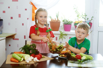 Children prepare salad vegetables . Happy kids in the kitchen . The concept of a healthy wholesome food