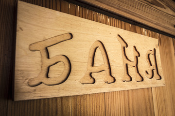 A wooden sign of a Russian bath close-up.