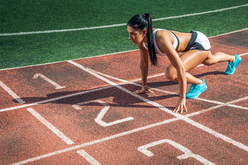 A young athletic woman stands in a low start for running in the stadium on a summer day