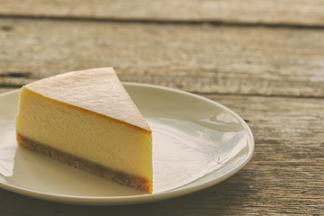 Homemade New York style cheesecake on white plate. Moist and smooth baked cheesecake. Delicious plain New York cheesecake with golden brown surface on rustic wood table with copy space for background.