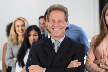 Successful Businessman Boss Over Businesspeople Group Background, Mature Leader With Business People Team Confident Hold Folded Hands Happy Smiling