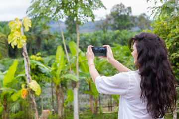 Woman Taking Photo Of Tropical Green Rain Forest Landscape On Cell Smart Phone Back Rear View