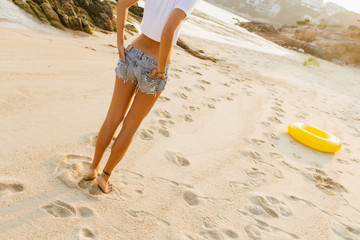 Close up of legs of beautiful fit woman in white shirt and jeans shorts walking away by the beach. Lady go to big inflatable ring. Beauty sunshine cute girl on a tropical sand beach with large stones.