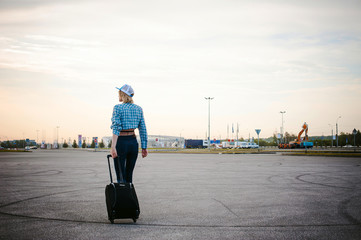 young slim woman dressed in blue checked shirt, cap and jeans, Will depart at dawn on summer day on freedom trip with black travel suitcase