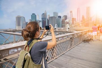 Tourist on Brooklyn bridge taking picture of scenery