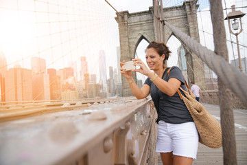 Tourist on Brooklyn bridge taking pictures with smartphone