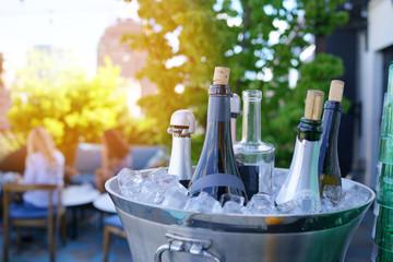 Wine bottles set in bucket, NYC rooftop