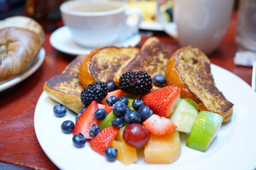 French toast with fruit salad set on restaurant table, NYC