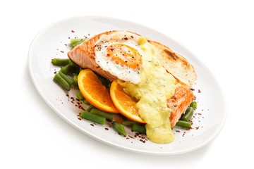Grilled salmon with sauce, fried egg and vegetables on white background