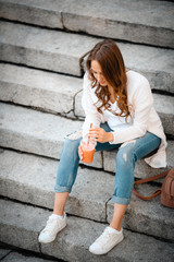 Woman sitting on stone steps, with healthy snack, cup strawberries, smoothie, fresh, outdoor