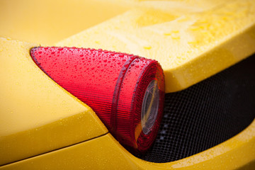 Yellow sport car tail light with rain drops