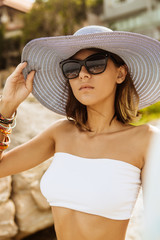 Close up of a lady in white skirt, top, sunglasses and summer straw hat in front of resort on rocks. Beauty cute girl on a tropical beach sea ocean shore with large stones. Outdoor summer lifestyle.