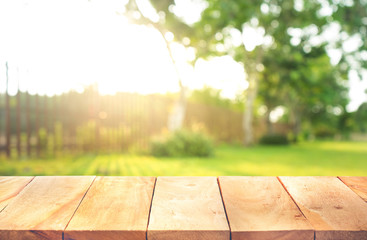 Wood table top with fence and grass in garden background.For  create product display or key visual layout