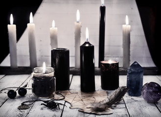 Mystic still life with black candles and pentagram on paper