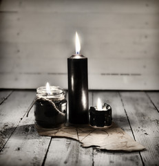Three black candles and old manuscript with pentagram on wooden table