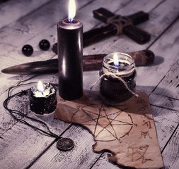 Still life with three black candles, old paper with pentagram and cross. Vampire killer concept
