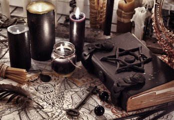 Toned still life with black magic book, demon paper and black candles