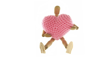Wooden mannequin hugging heart knit with yarn