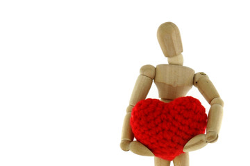 Wooden mannequin holding heart knit with yarn